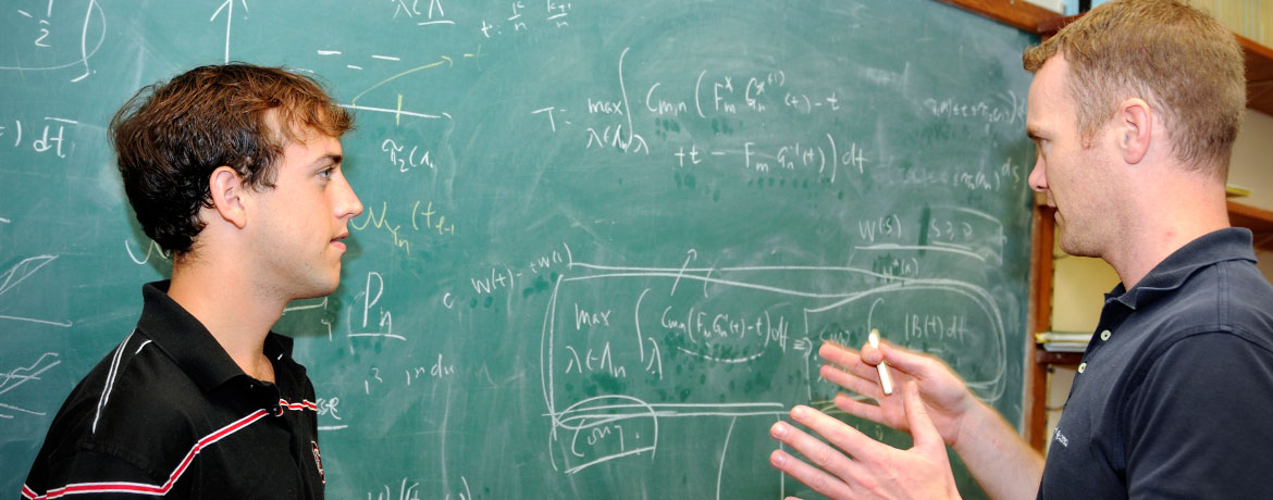 two students discussing a solution in front of a blackboard